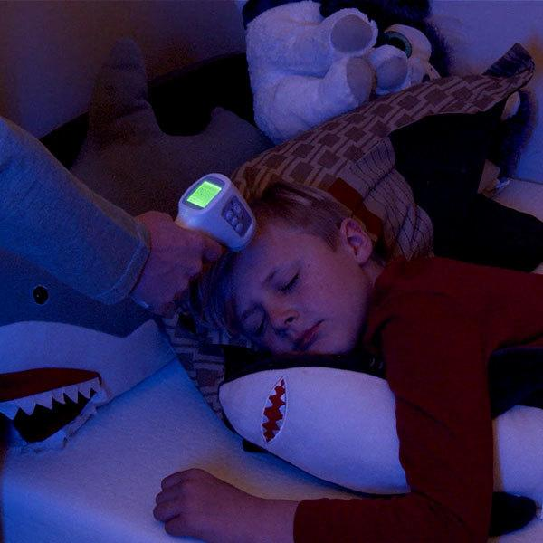mom takes child's temperature while he is sleeping