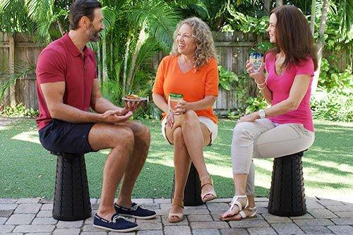 Three people smiling and sitting on Ninja Stools outside