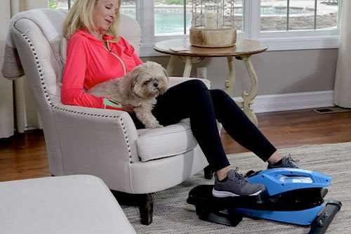 Woman pedaling on Blu Tiger while sitting down with dog on lap