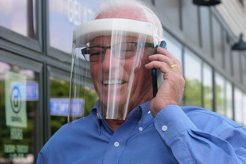 Elderly man wearing Fresh View Shield while talking on cell phone
