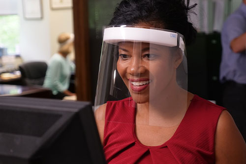 Woman wearing Fresh View Shield in office working on computer
