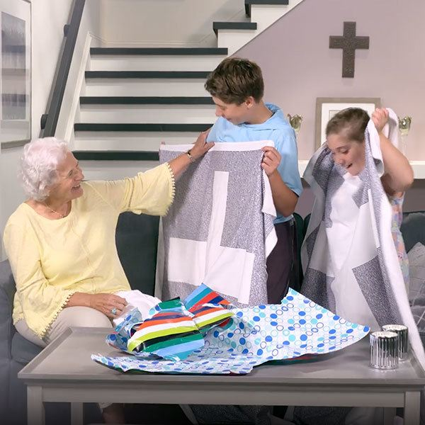 children unwrapping believer blanket gift