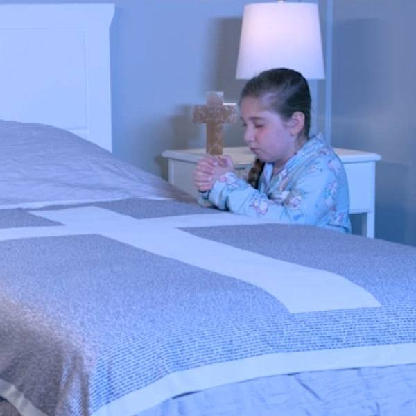 girl praying at bedside with believer blanket