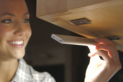 Woman sticking Atomic Sun Blade to underside of cabinet with magnet mount