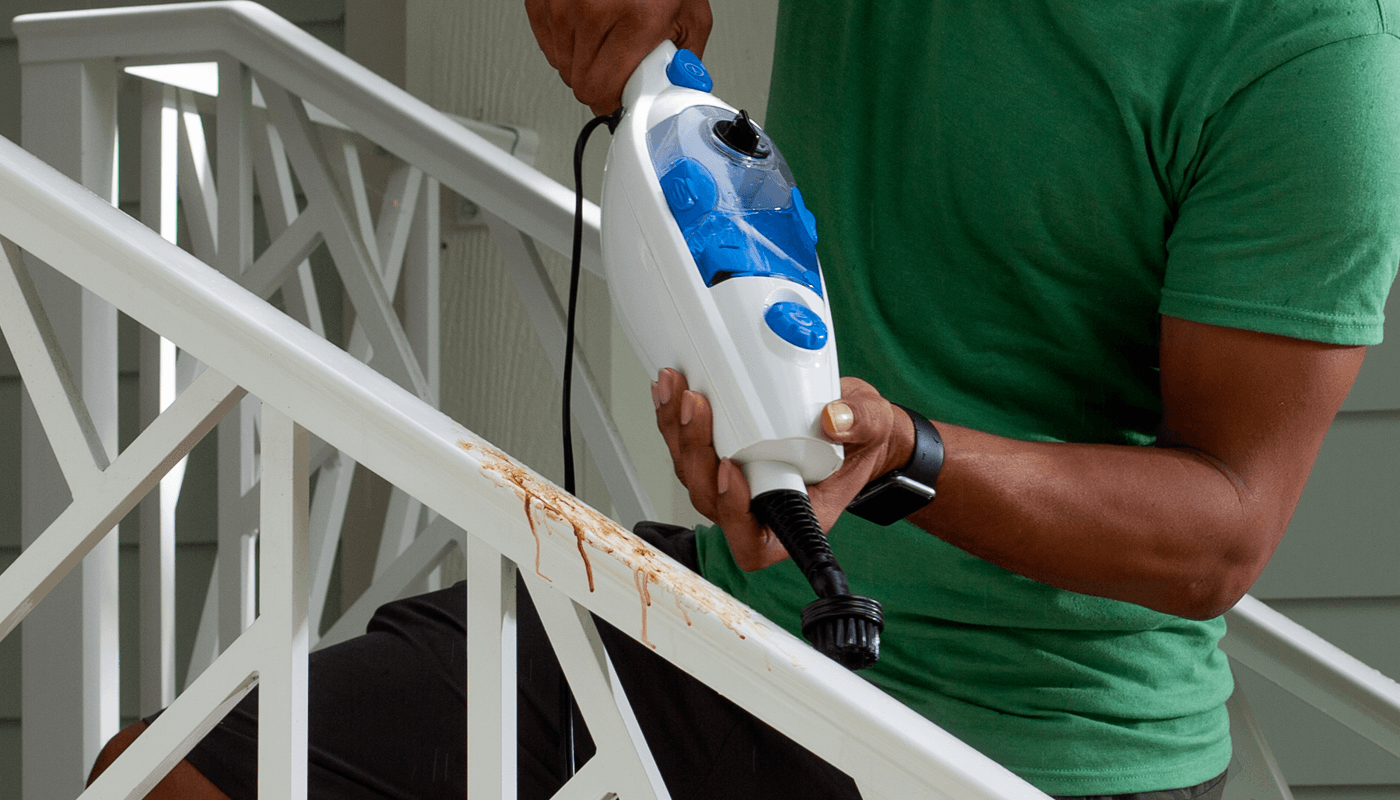 person cleaning stairway railing with cleanica