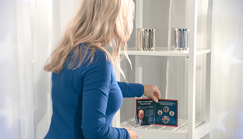 woman displaying coin collection on shelf