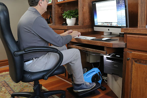 Man pedaling on Blu Tiger while sitting down and working in home office